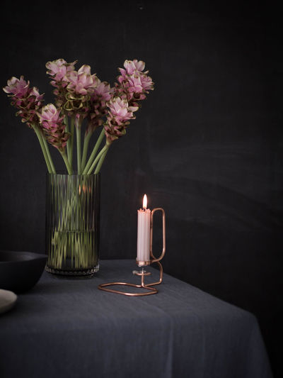 Lit Candle With Flowers In Vase On Table