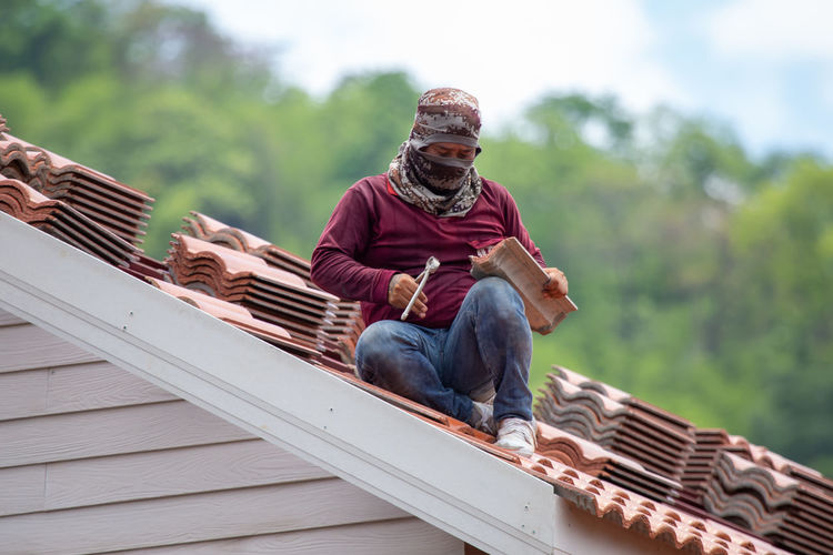 Low angle view of man sitting on roof