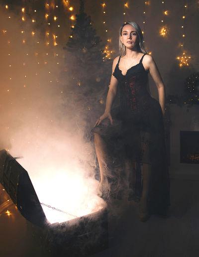 Woman standing by illuminated light at night