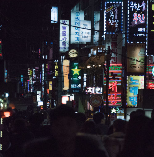 City Night Illuminated Architecture Building Exterior Built Structure City Life Communication Advertisement Street Text Neon Commercial Sign Real People Incidental People Sign Billboard Building Nightlife Skyscraper Seoul Korea The Art Of Street Photography The Street Photographer - 2019 EyeEm Awards