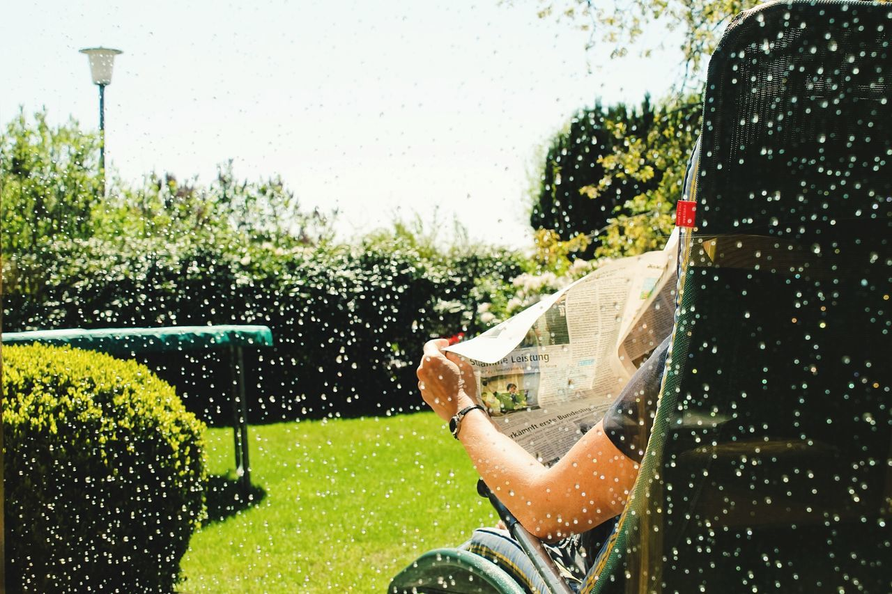 Cropped Image Of Person Reading Newspaper Seen Through Wet Window