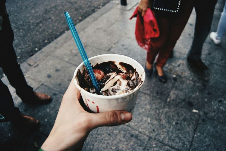 Cropped image of hand holding frozen yoghurt in disposable cup at city