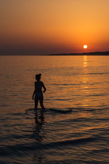 Silhouette girl standing in sea against sky during sunset