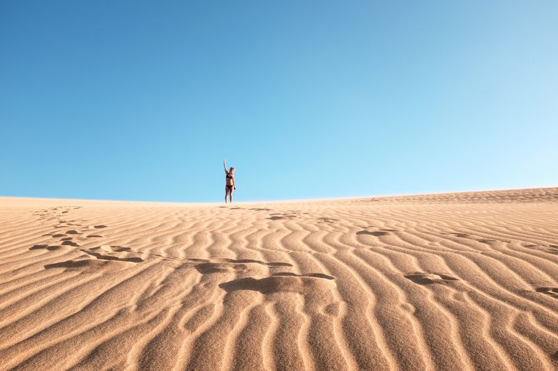 Woman Standing On Sand Dune Against Clear Blue Sky