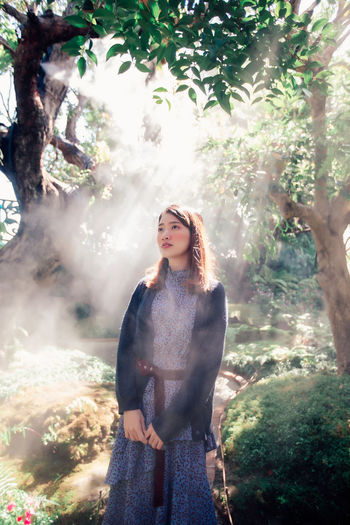 Beautiful pretty woman standing with in the forest with fog and rays of sunlight