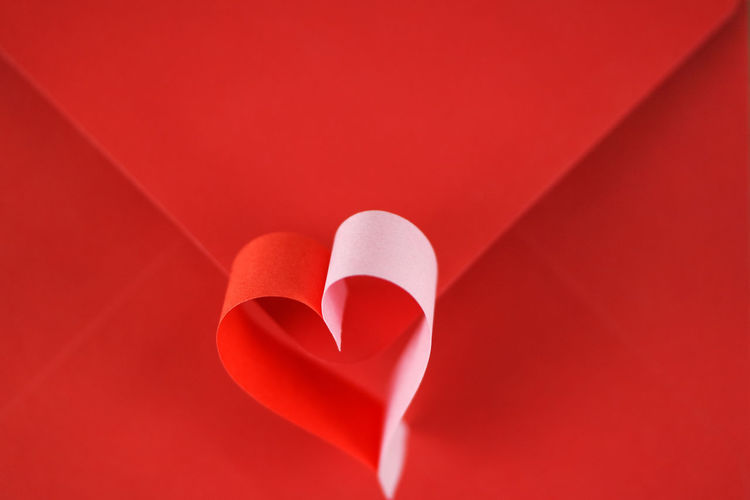 Close-up of heart shape papers on red table