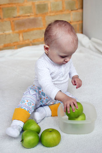 Cute baby girl playing with apple while sitting on bed