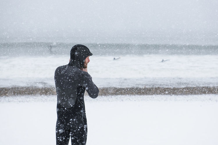 Woman standing in sea during winter