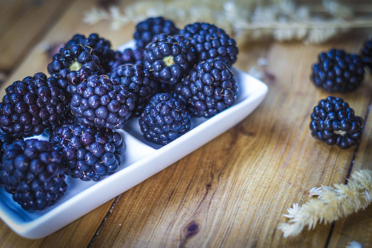 High angle view of blackberries in plate on table