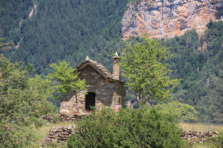 Old house on field against mountains