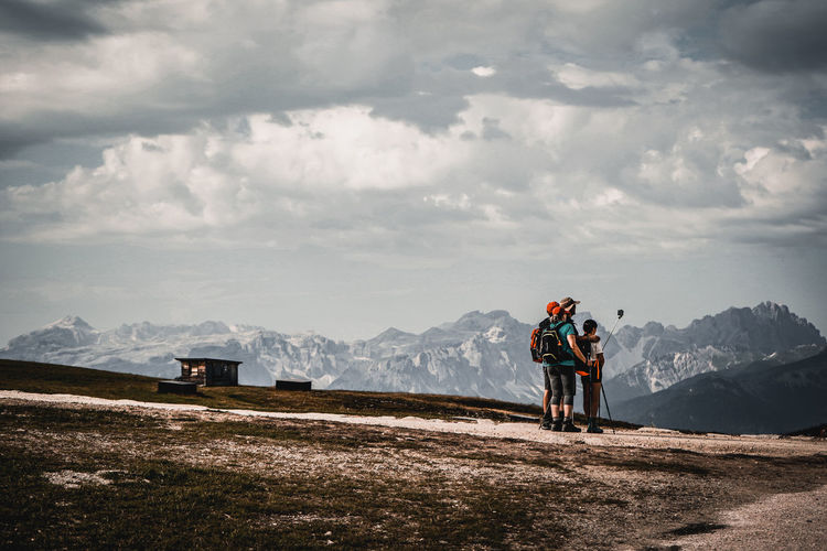 People riding on mountain against sky