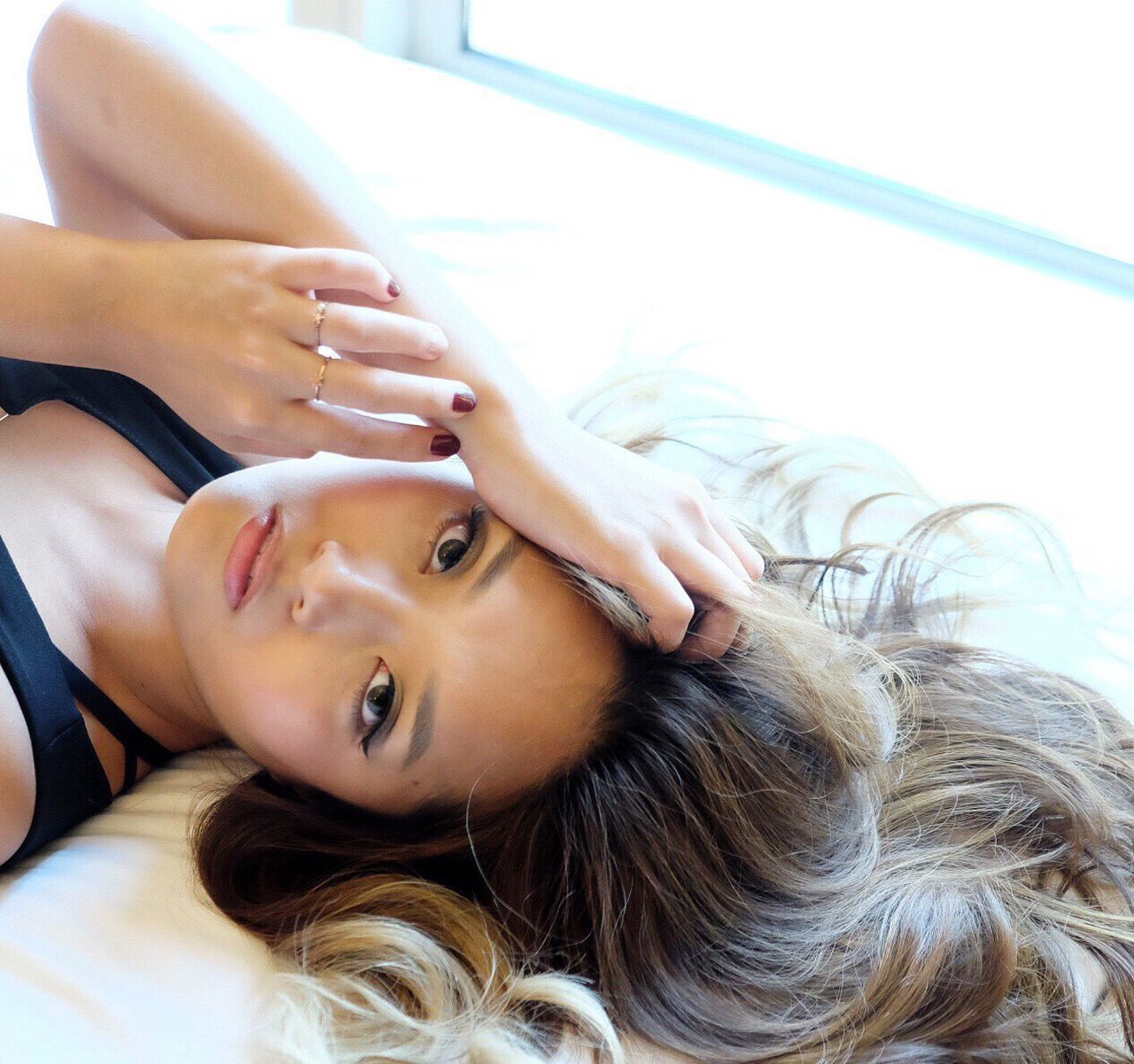 Portrait Of Beautiful Woman Lying On Bed At Home