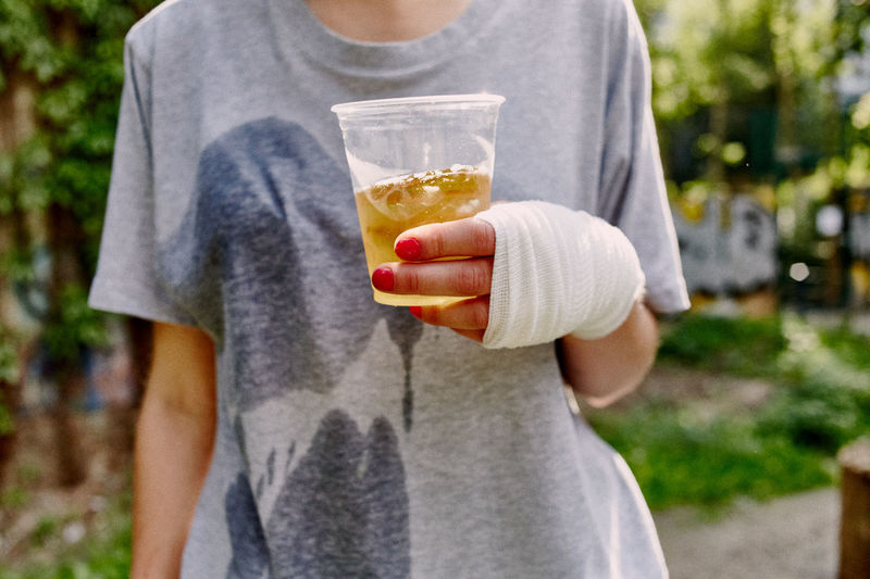 Midsection of woman with bandage on hand holding drink