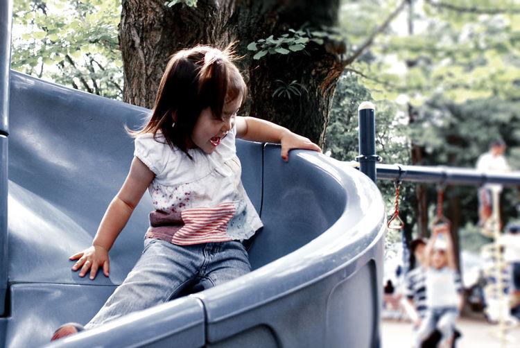Playful girl enjoying slide at park