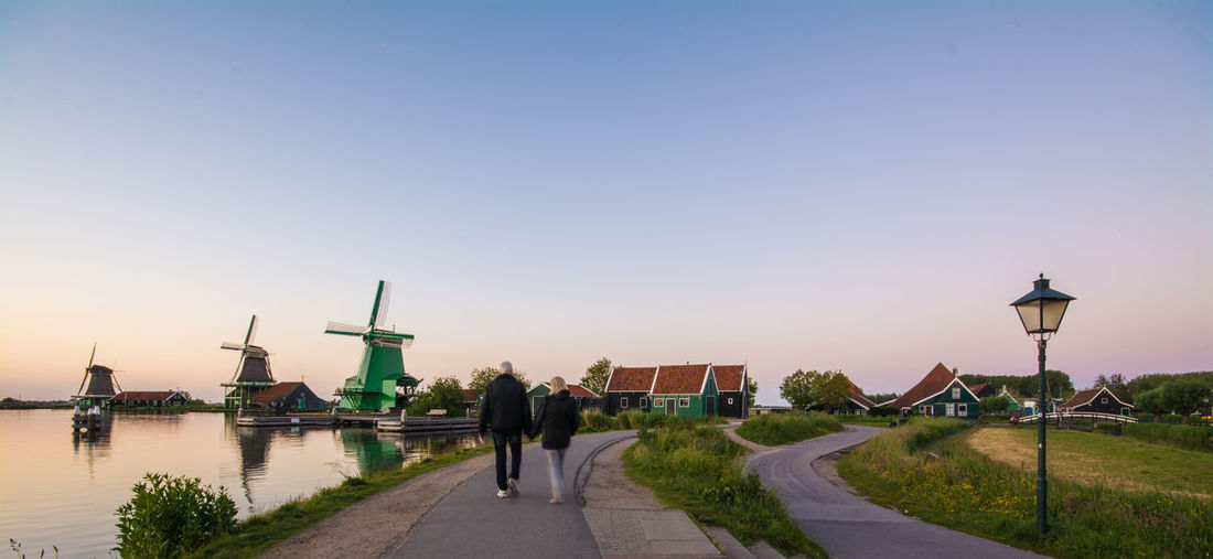 Traditional Dutch windmills with canal close Blue Built Structure Clear Sky Day Grass Lifestyles Nature Outdoors Road Sky Street Light The Way Forward Travel Destinations Walkway