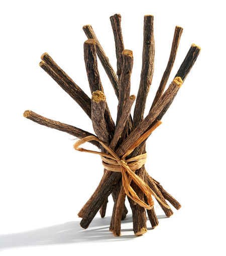 Bundle of dried licorice pr liquorice roots tied with raffia for flavoring candy and desserts on a white background Bundle Healing Liquorice Natural Plant Alternative Curative Food Licorice Roots Shadow Studio Shot Tied Upright