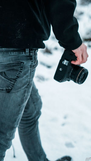 Winter Snow Casual Clothing Holding Midsection Cold Temperature Standing Jeans Day Focus On Foreground Men Clothing Outdoors Gun Human Hand Low Section Warm Clothing