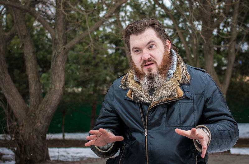 Confused bearded man wearing jacket against trees during winter at park