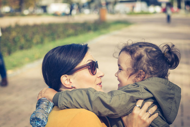 Smiling mother and daughter spending leisure time at park