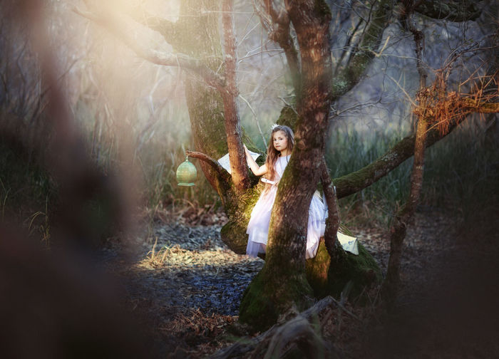 Pretty little prinzess with long hair in a dark fairy forest, playing the flute