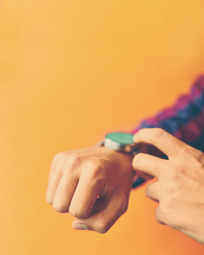 Cropped hands against yellow background