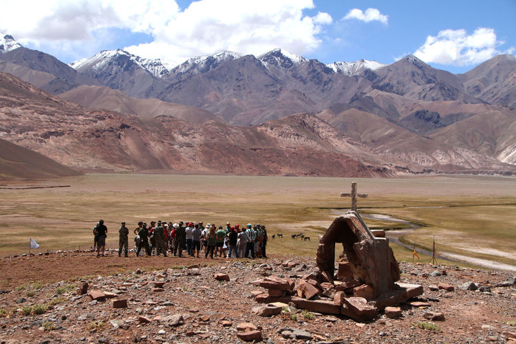 People On Field By Mountains Against Sky