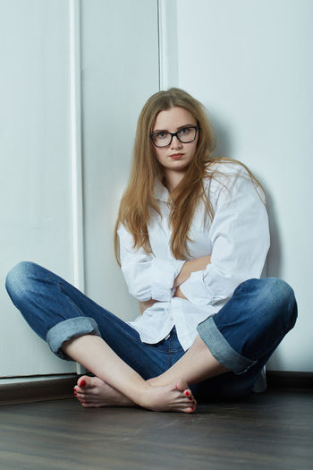 Beautiful young woman sitting against wall at home
