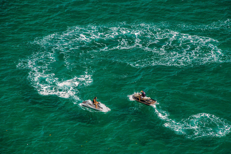 High Angle View Of Men On Jet Boat In Sea