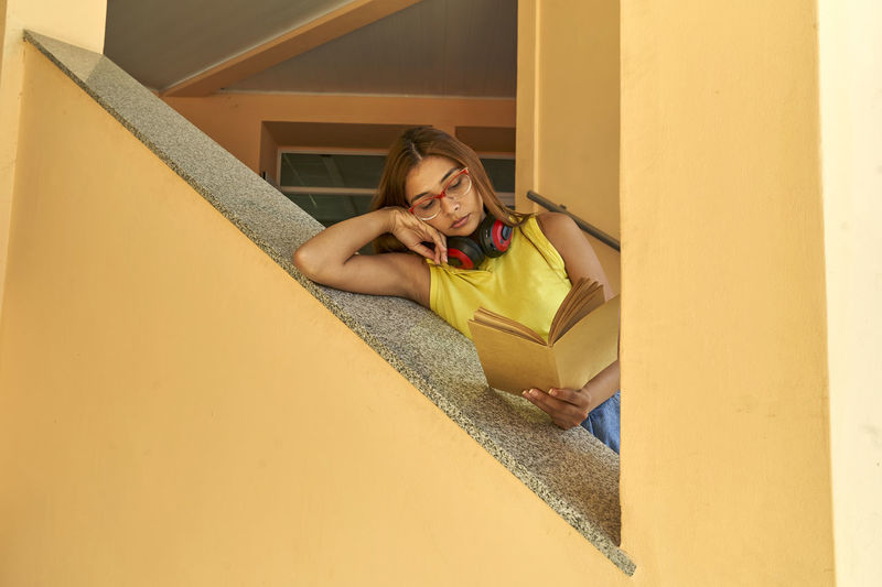 Portrait of young woman lying down on staircase