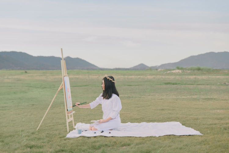 Side view of woman sitting on field against sky