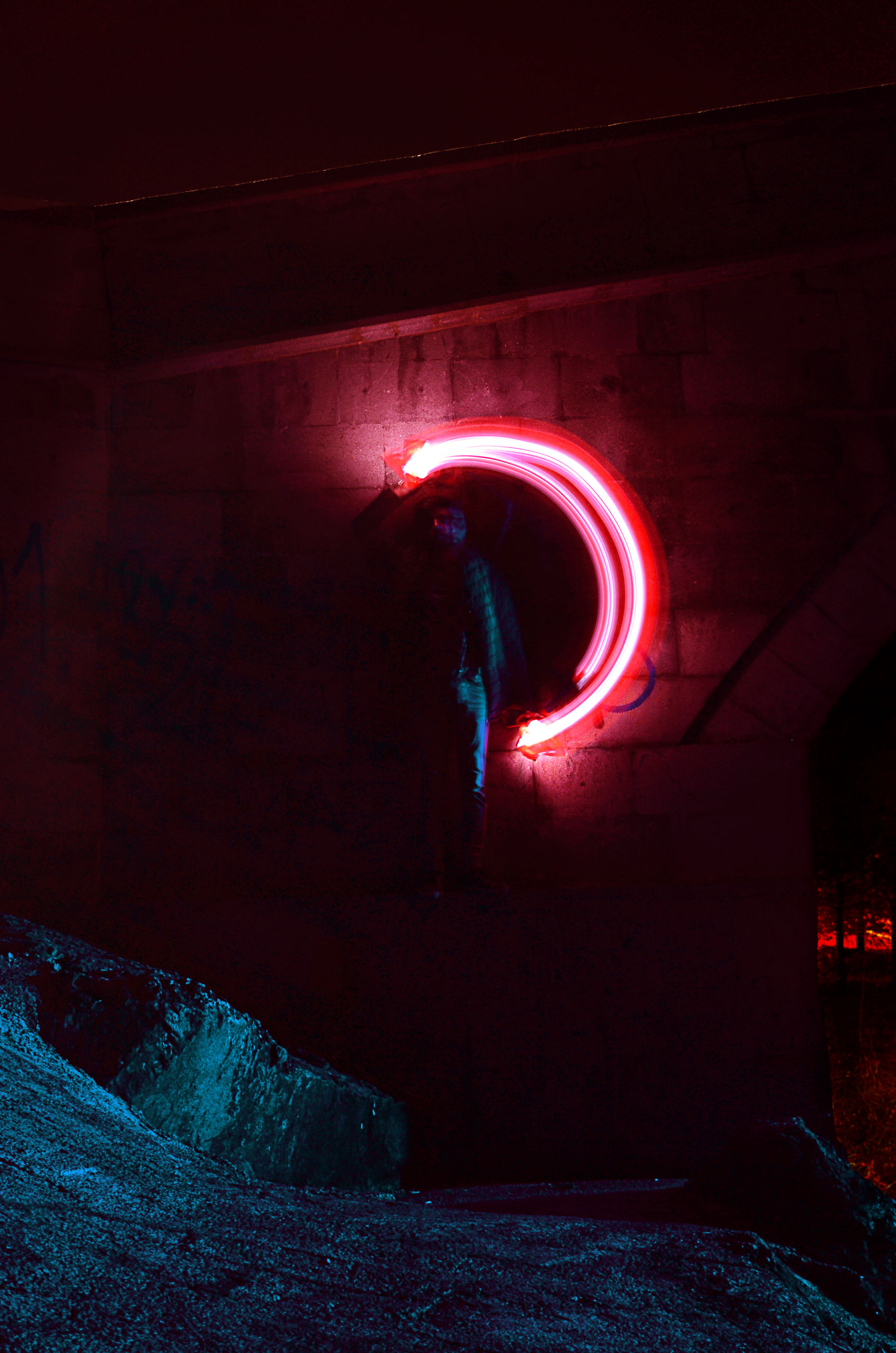 illuminated, night, real people, architecture, glowing, red, one person, built structure, tunnel, motion, wall - building feature, standing, indoors, arch, men, light - natural phenomenon, lifestyles, long exposure, lighting equipment, light