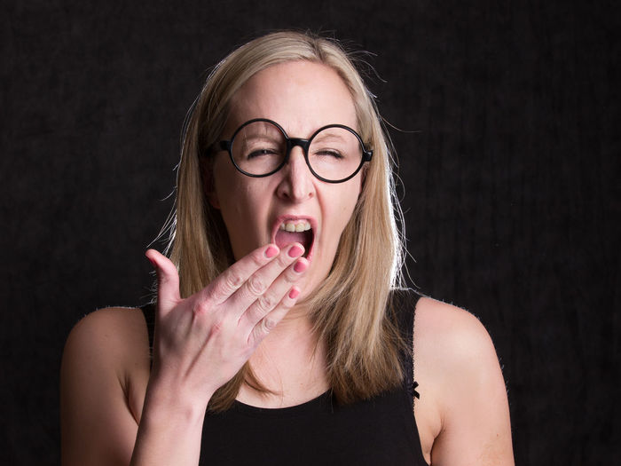 Tired Hand Hairstyle Beautiful Woman Headshot Human Body Part Young Women Emotion Adult Front View Mouth Portrait Mouth Open Women Young Adult Blond Hair Indoors  Glasses Hair One Person Eyeglasses  Black Background Studio Shot Indoors