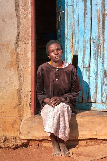 Portrait Of Woman Sitting On Doorway