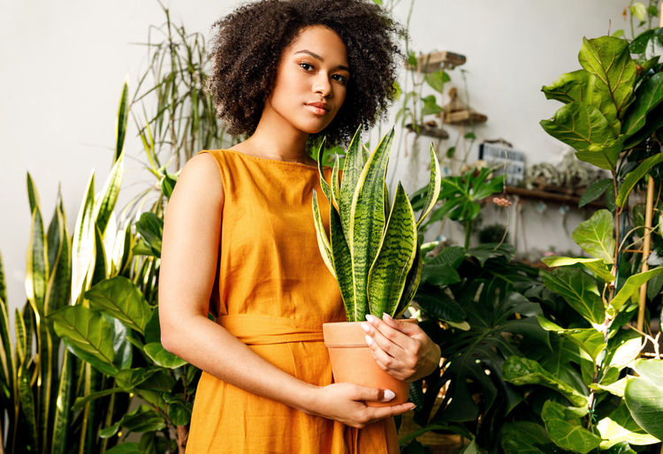 Portrait of teenage girl holding potted plant amid plants