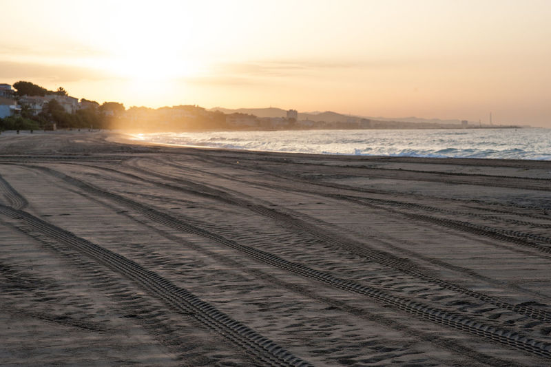 Scenic View Of Tire Tracks On Beach Against Sky During Sunset