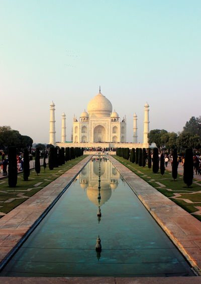 Fountain in front of taj mahal against clear sky