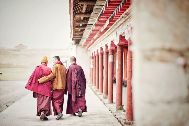 Rear View Of Monks Walking On Walkway By Temple