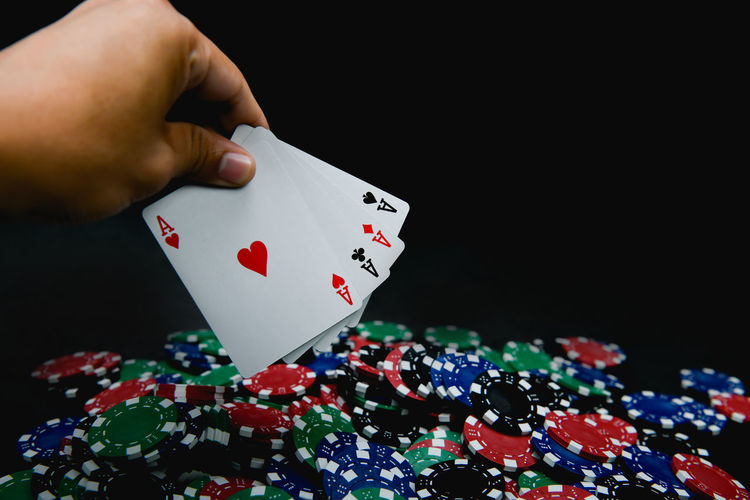 Cropped Hand Holding Playing Cards Over Gambling Chips Against Black Background