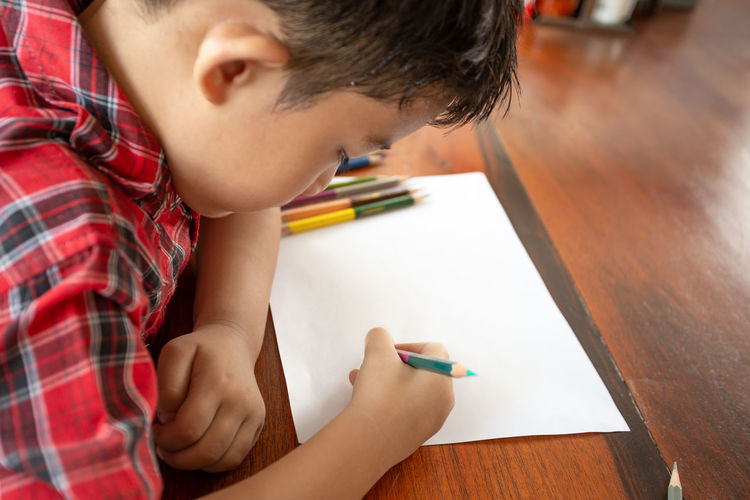 Cute Boy Drawing In Paper At Home