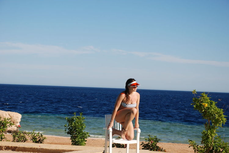 Full length of beautiful woman sitting on chair against sea and sky