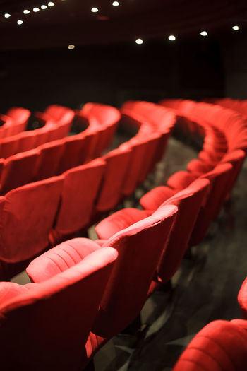 red theater seats Red Seat Auditorium In A Row Movie Theater Arts Culture And Entertainment Chair Indoors  Film Industry Performance Lighting Equipment MOVIE Stage Theater Vertical Empty Cinema Interior Event Public Audience Indoors  Amusement  Close-up Detail