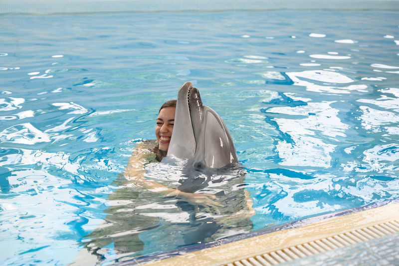 Smiling young woman with dolphin swimming in pool
