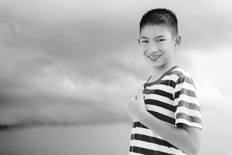 Portrait of smiling teenage boy standing against cloudy sky