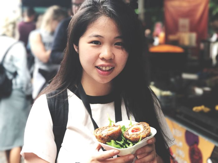 Close-Up Portrait Of Young Woman Having Street Food