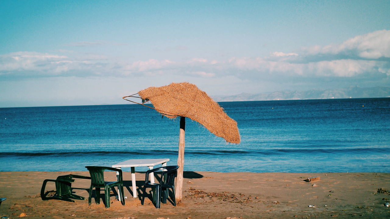 sea, water, horizon over water, horizon, sky, beach, beauty in nature, land, scenics - nature, cloud - sky, tranquil scene, tranquility, chair, seat, sand, nature, table, no people, idyllic