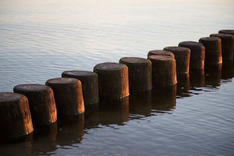 Baltic Sea Beauty In Nature Close-up Day In A Row Jetty Marina Nature No People Ostsee Outdoors Pier Reflection Repetition Rippled Side By Side Standing Water Tranquil Scene Tranquility Usedom Water Water Surface Waterfront Wood - Material Wooden Post