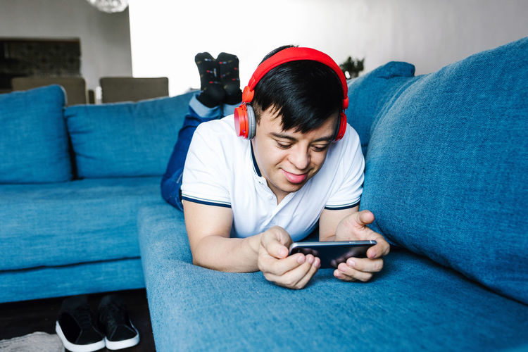 Man using mobile phone while sitting on sofa