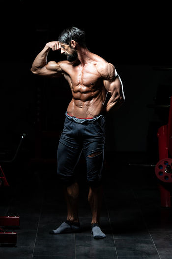 Full length of shirtless man holding camera while standing against black background