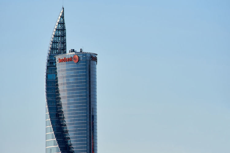 Riga, Latvia - May 04, 2017: Modern glass skyscraper of Swedbank office against blue sky in Riga city. Latvia, Northern Europe Architecture Blue Building Exterior Built Structure City City Center Clear Sky Day Downtown Glass Headquarter Highrise Latvia Riga Modern Architecture No People Northern Europe Office Building Outdoors Riga Sky Skyscraper Swedbank Tower Urban Skyline