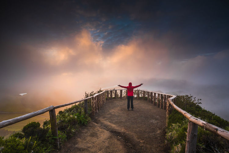 Rear view of woman arms outstretched standing on mountain peak